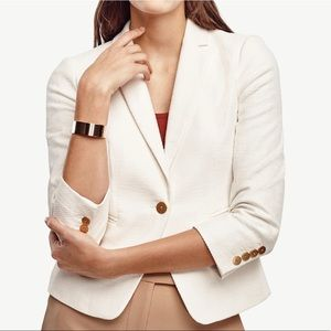 White blazer textured with gold buttons